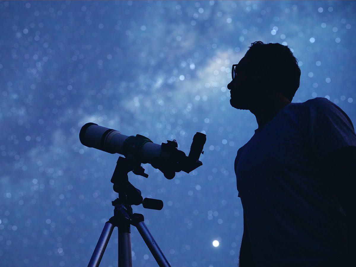 Man with telescope stargazing outside.