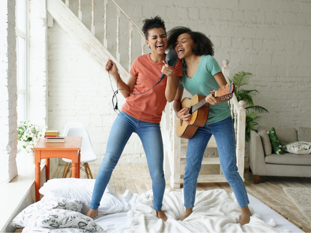 Two female friends having a dance party in their home