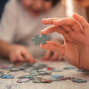 Child finishing jigsaw puzzle with parents