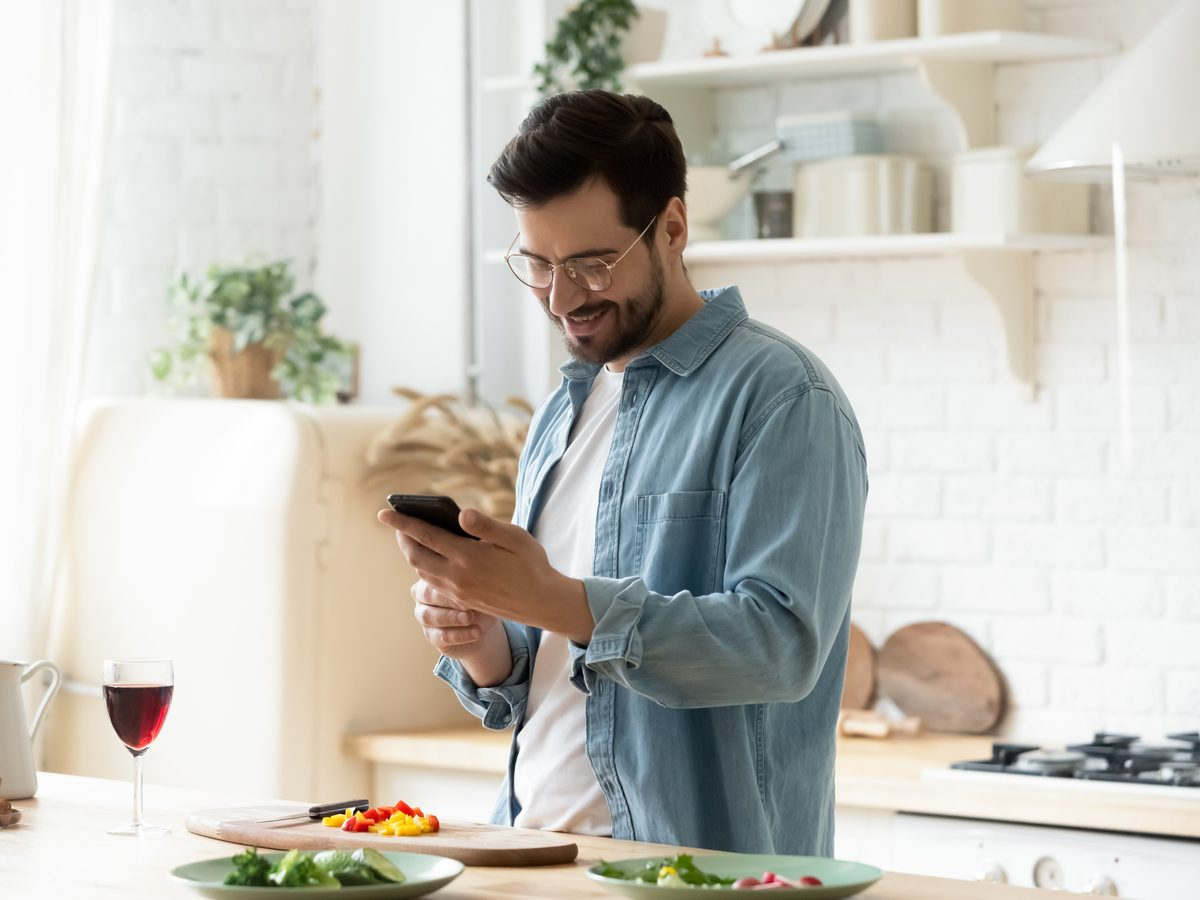 Millennial male in his kitchen using his smartphone