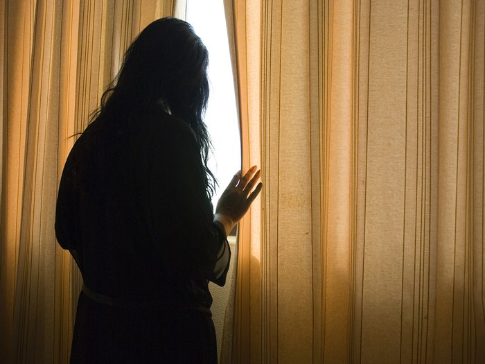 Signs you're not getting enough sunlight - woman peeking through curtains