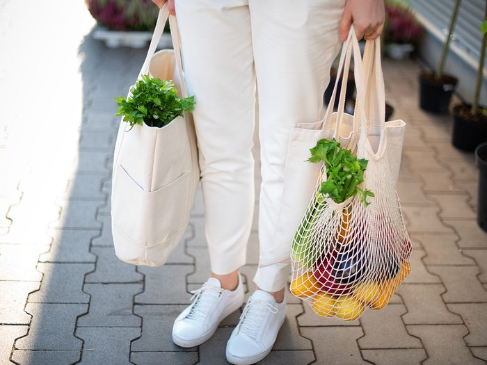 Girl is holding mesh shopping bag and cotton shopper with vegetables without plastic bags at farmers market. Zero waste, plastic free concept. Sustainable lifestyle. Banner