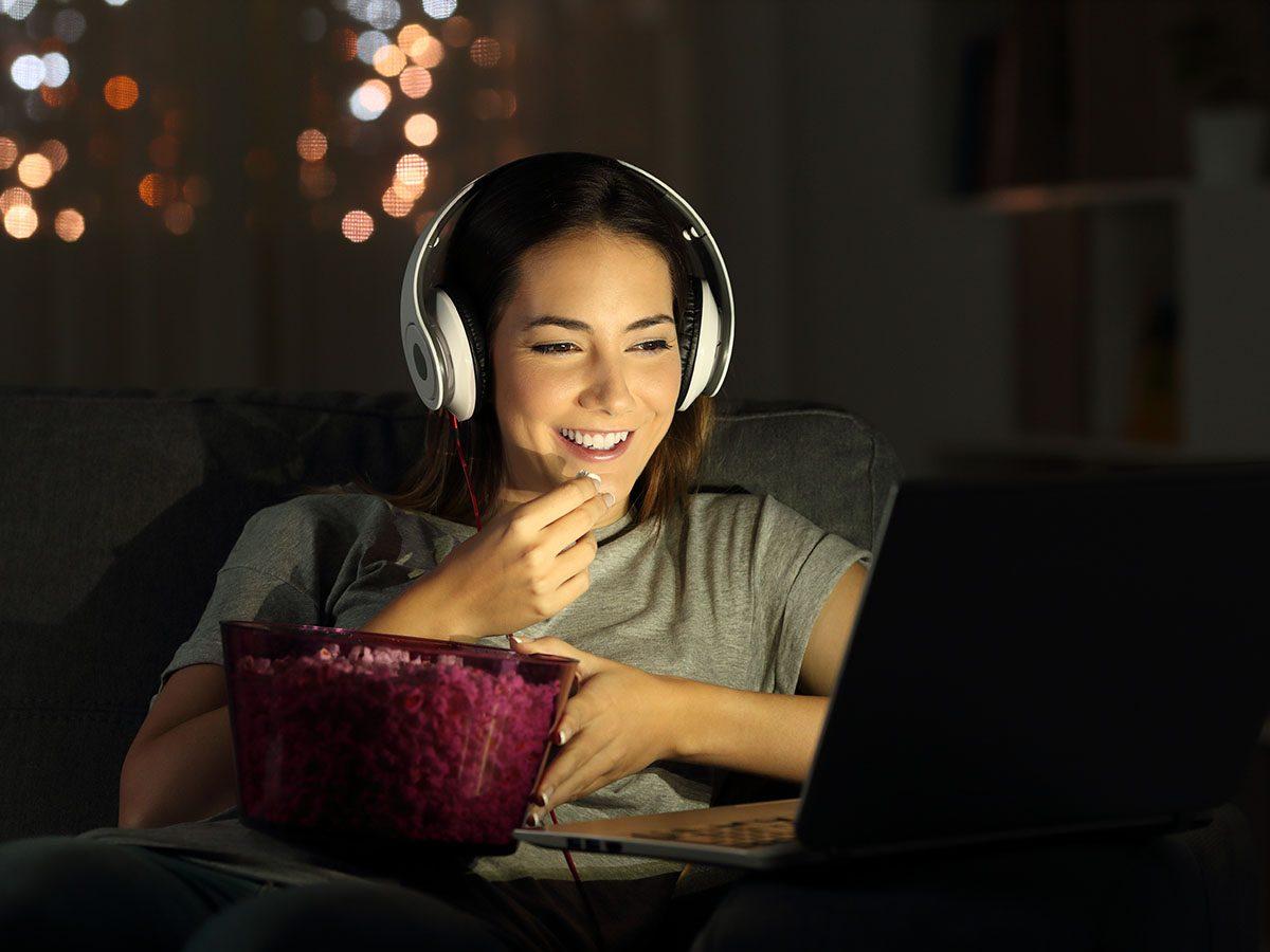 women watching film on laptop while eating popcorn.