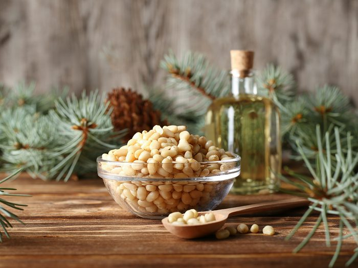 mosquito repellent plants - Cedar pine nuts in glass bowl with cones, oil, spoon, cedar brunch on wooden background
