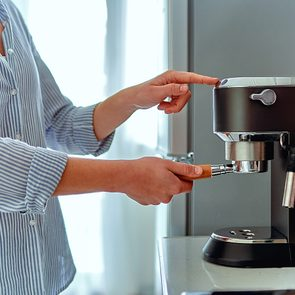Coffee maker mistakes - Female hands holding portafilter and making fresh aromatic coffee at home using a modern coffee maker