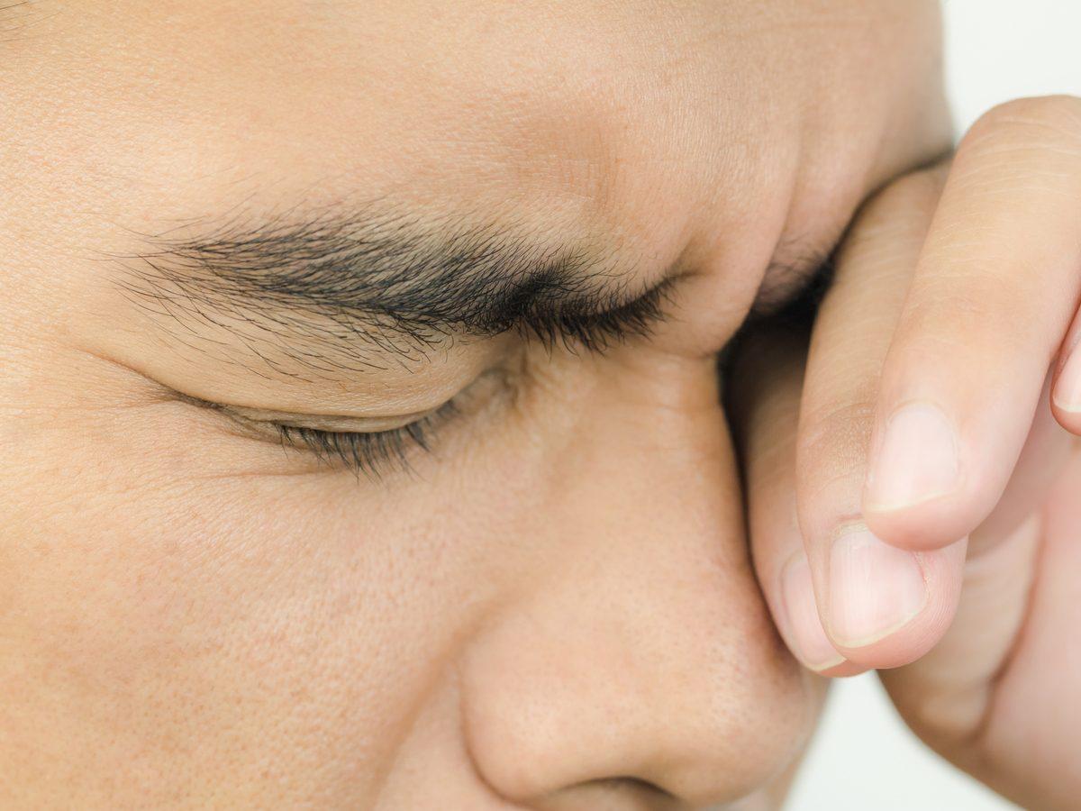 Man rubbing his irritated eyes