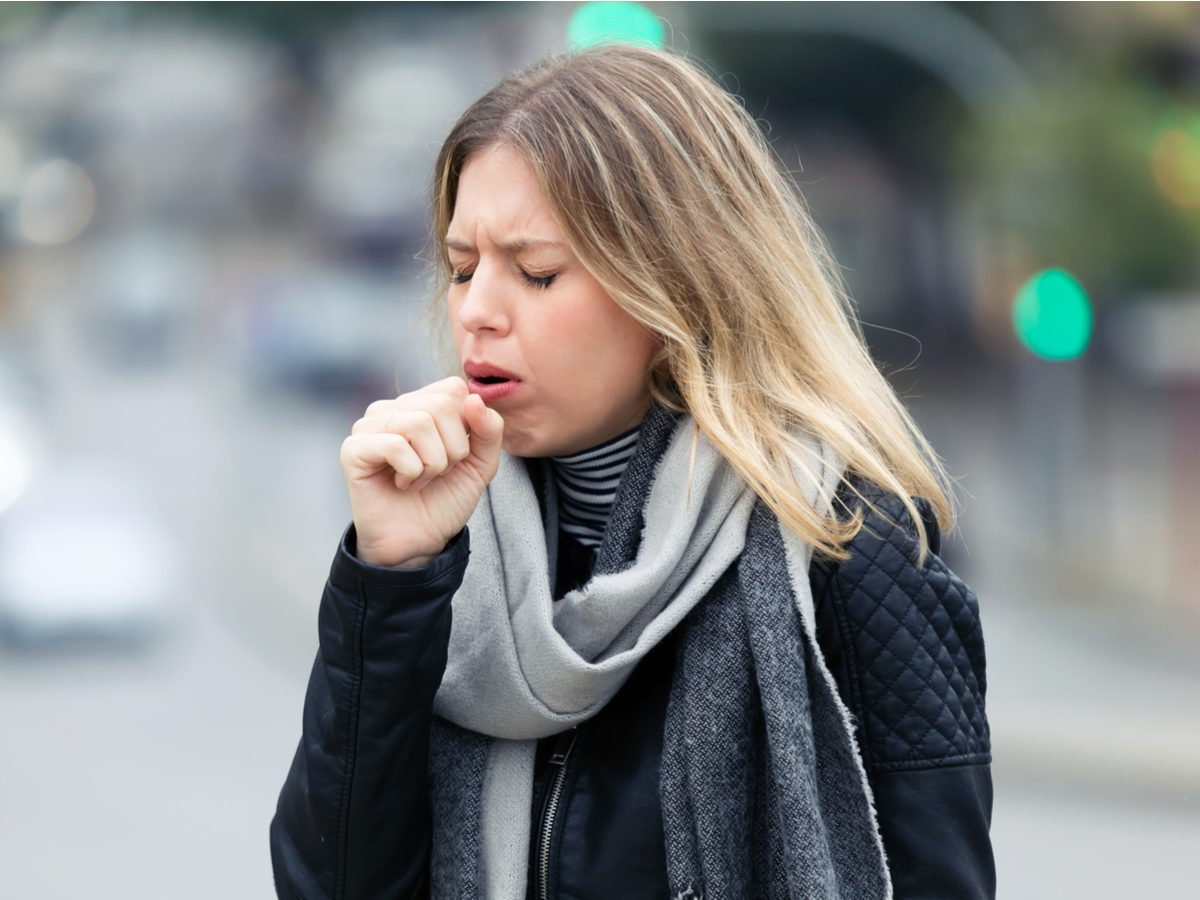 Young businesswoman coughing on the street