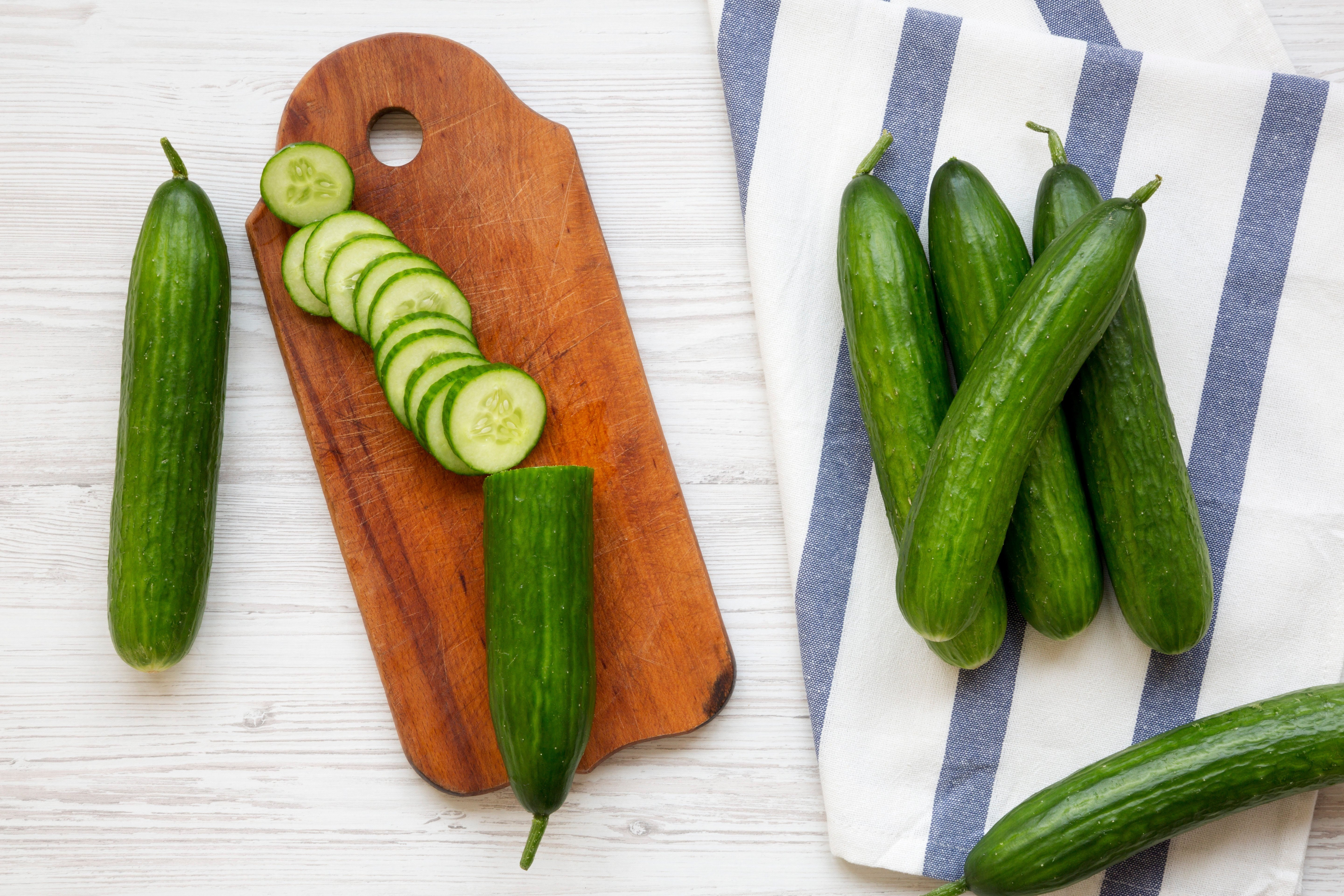 Fresh raw green cucumbers, top view. Flat lay, from above, overhead. White wooden background.