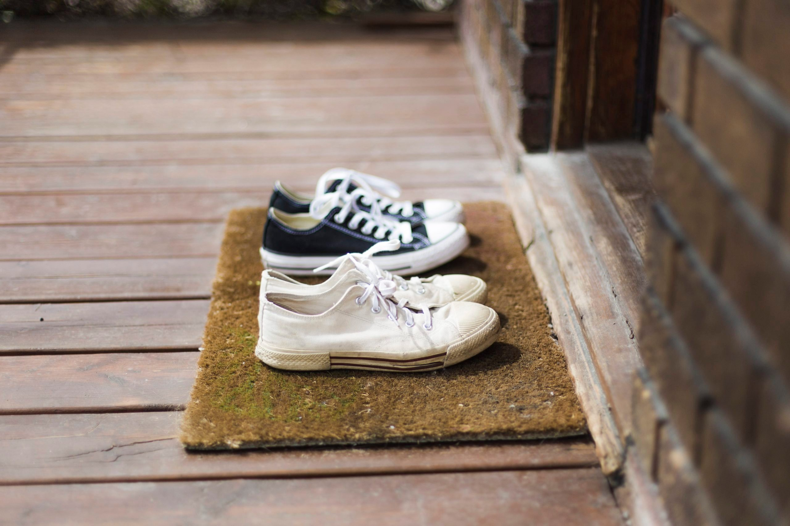 Two pairs of black and white sneakers shoes on a porch