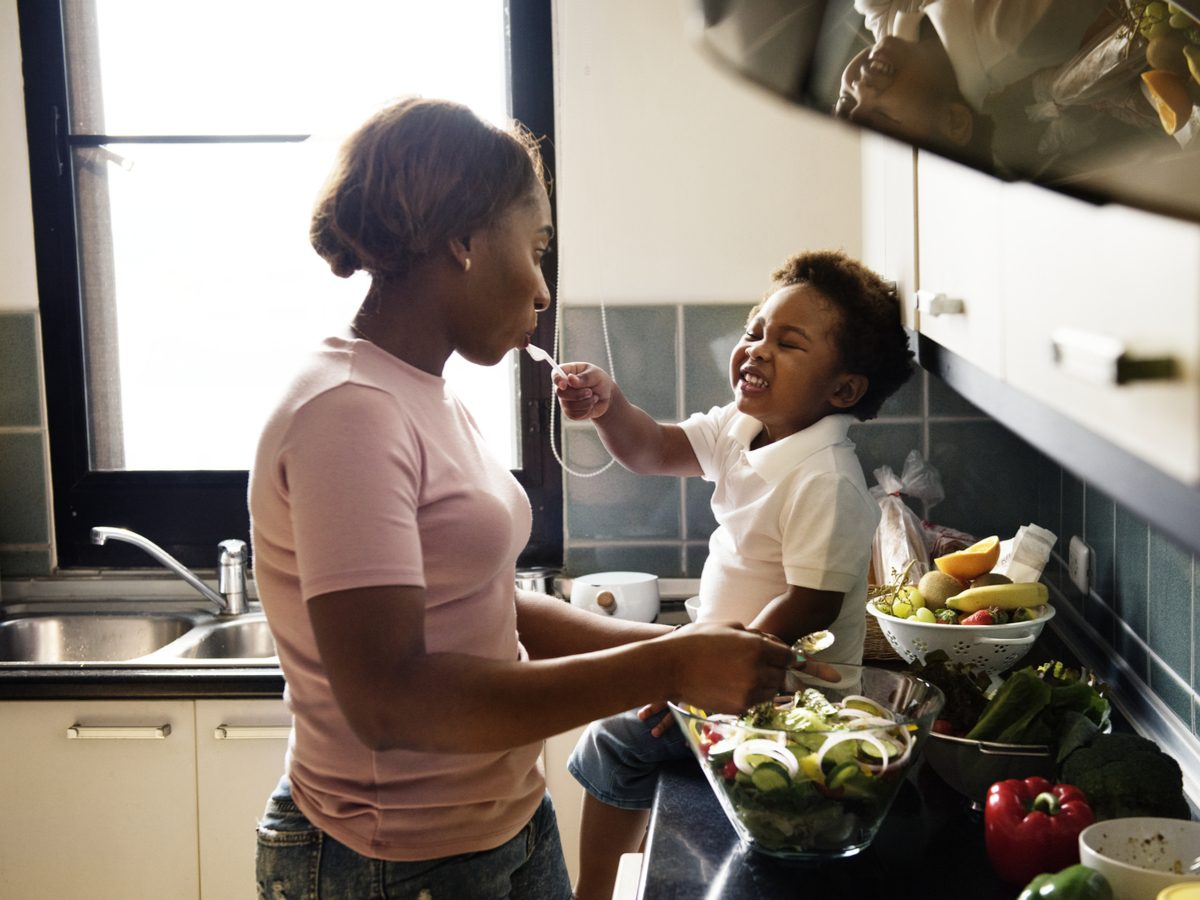 Mom cooking food with young daughter
