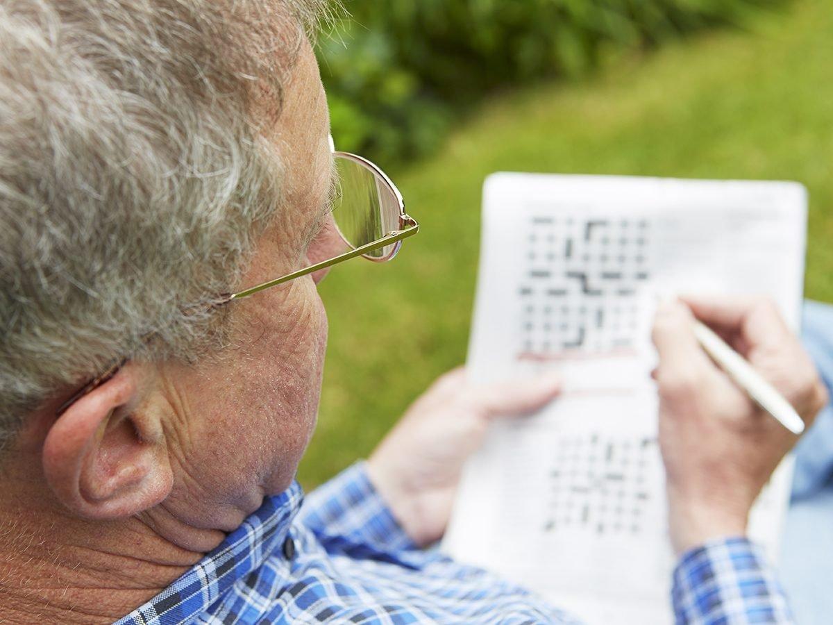 Things that slow down aging - senior man doing crossword