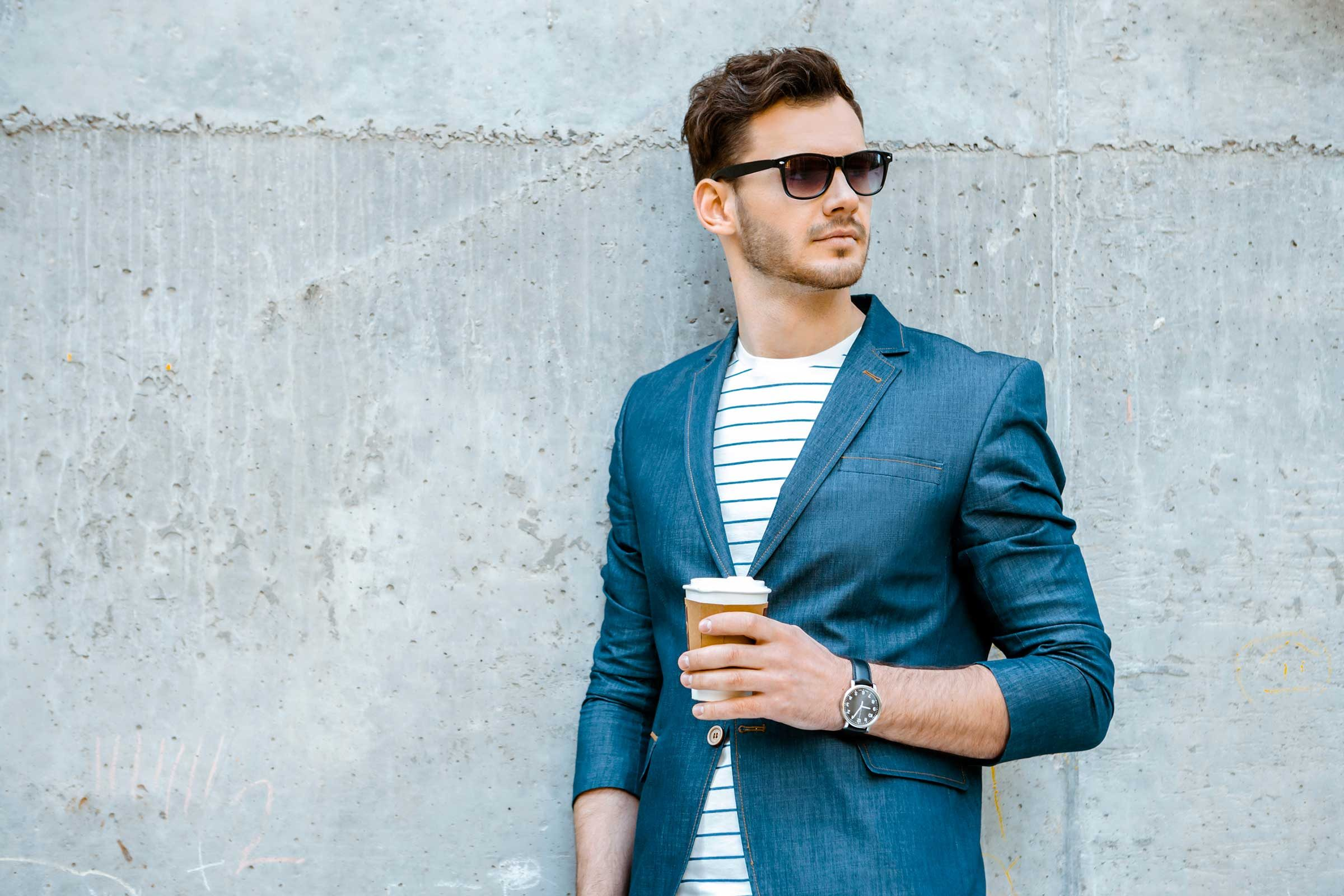 man wearing sunglasses and holding cup of coffee