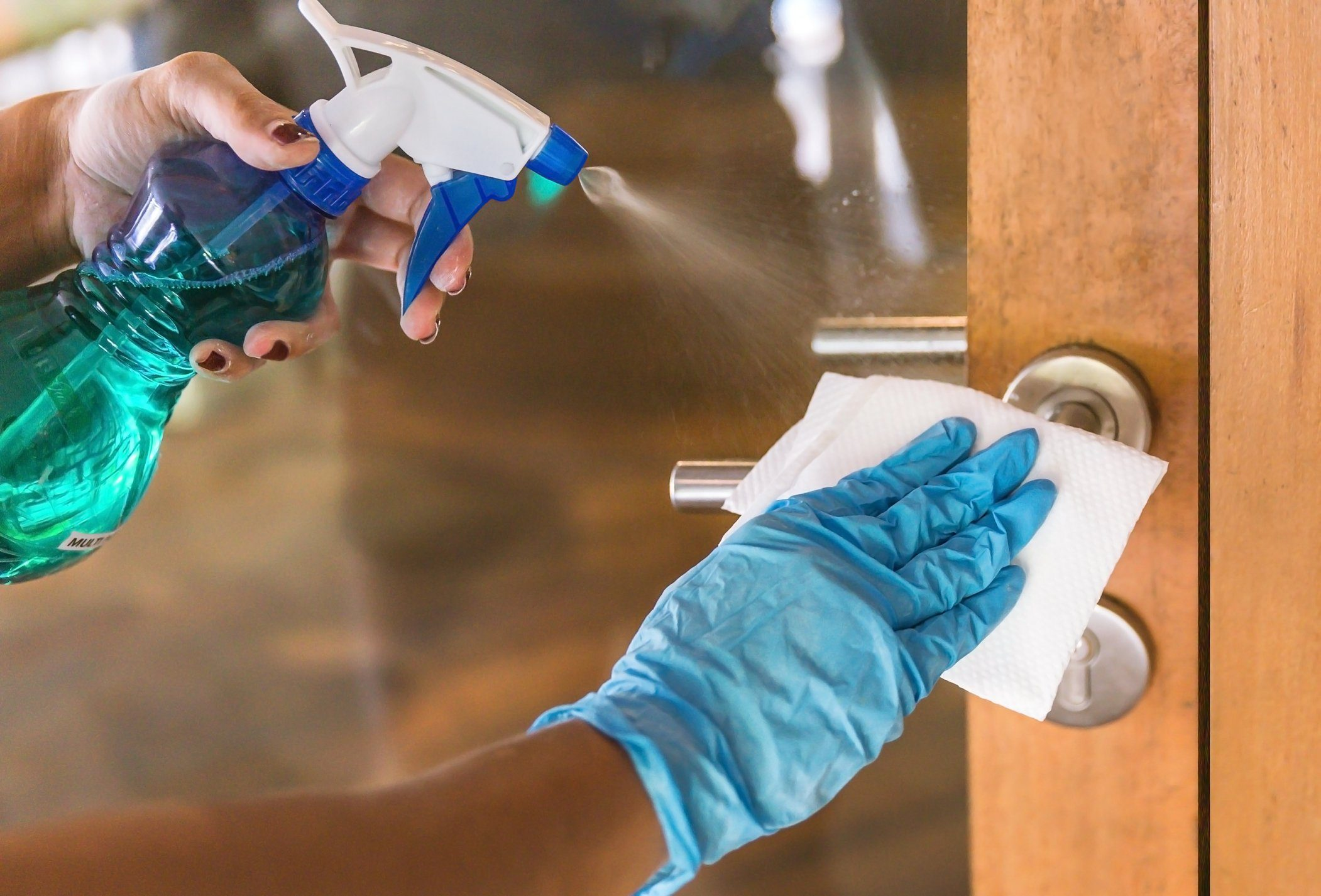 Young Asian woman sanitizing door handle with disinfectant