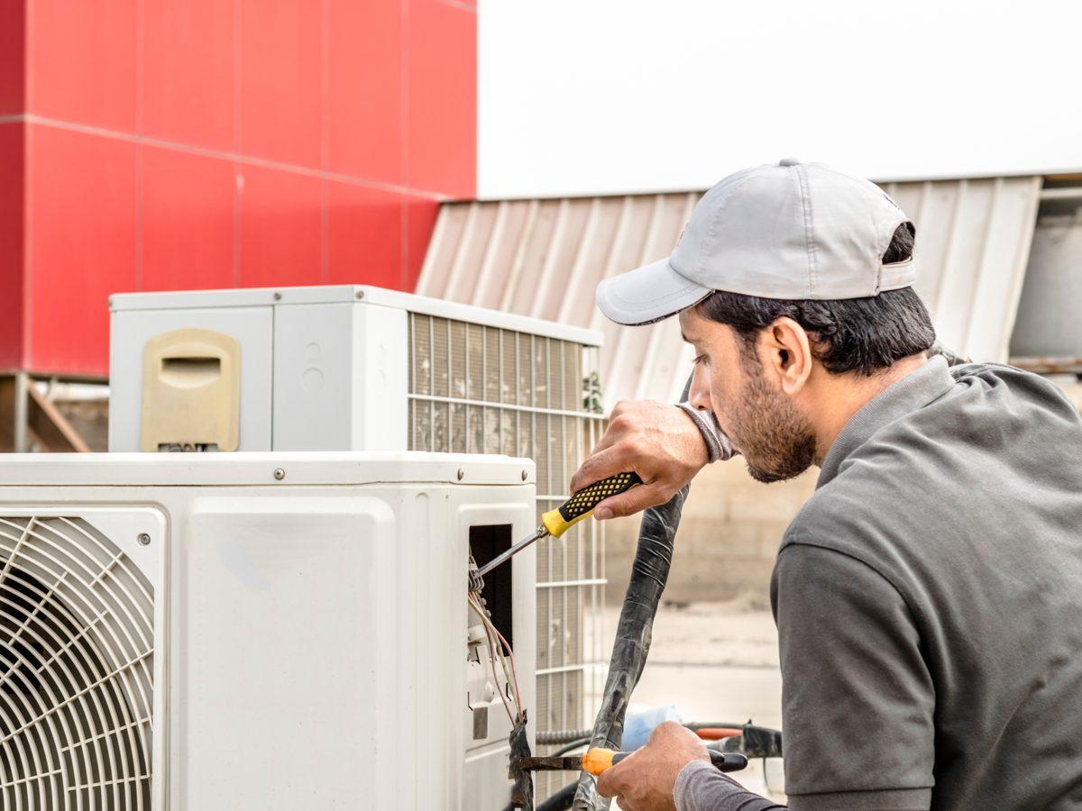 Electrician repairing air conditioning unit