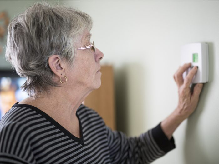 Senior woman adjusting thermostat in her apartment