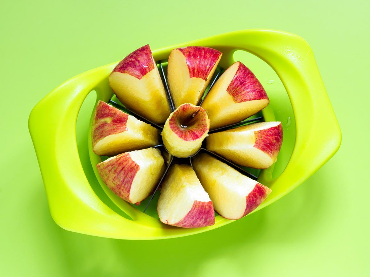 Apple on a green surface is sliced open with a green apple corer.