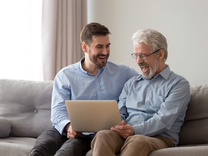 Bad dad jokes - Happy young man relax sit on couch with senior dad have fun watching funny video on laptop together, smiling elderly father and grown son rest on weekend laugh using internet on computer a home