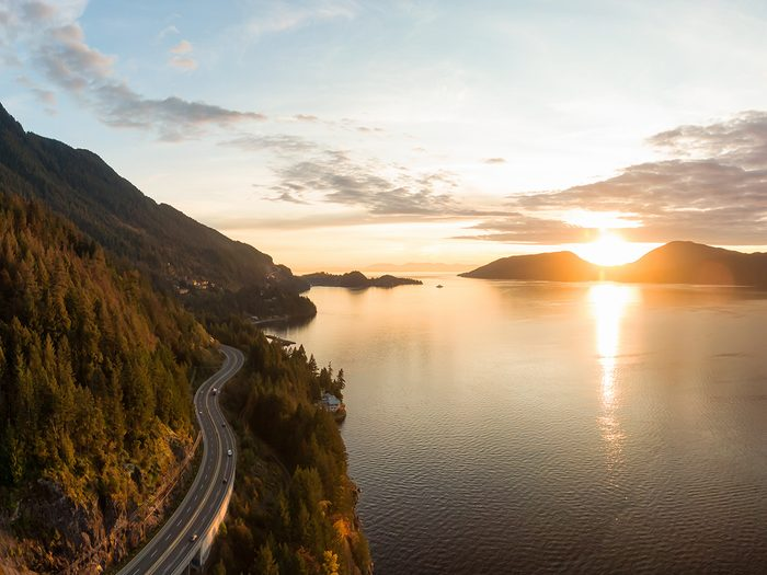 Canada road trip - Sea to Sky Hwy in Howe Sound near Horseshoe Bay, West Vancouver, British Columbia, Canada. Aerial panoramic view during a colorful sunset in Fall Season.