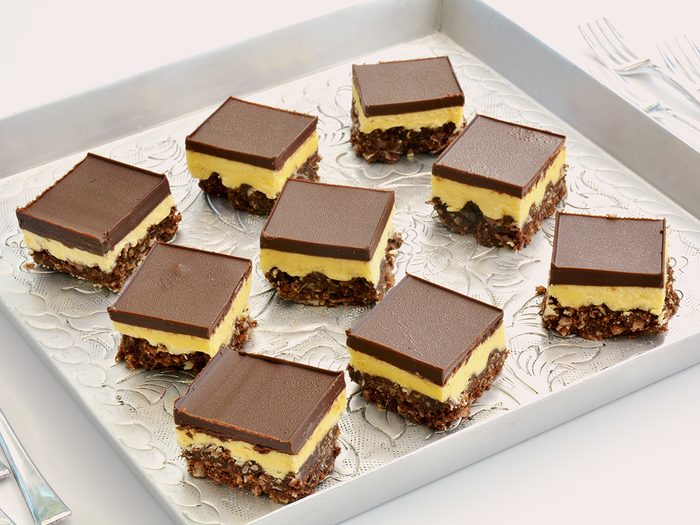Canadian Food - Fresh baked Nanaimo bars on vintage embossed metal tray and tiny forks in horizontal format.
