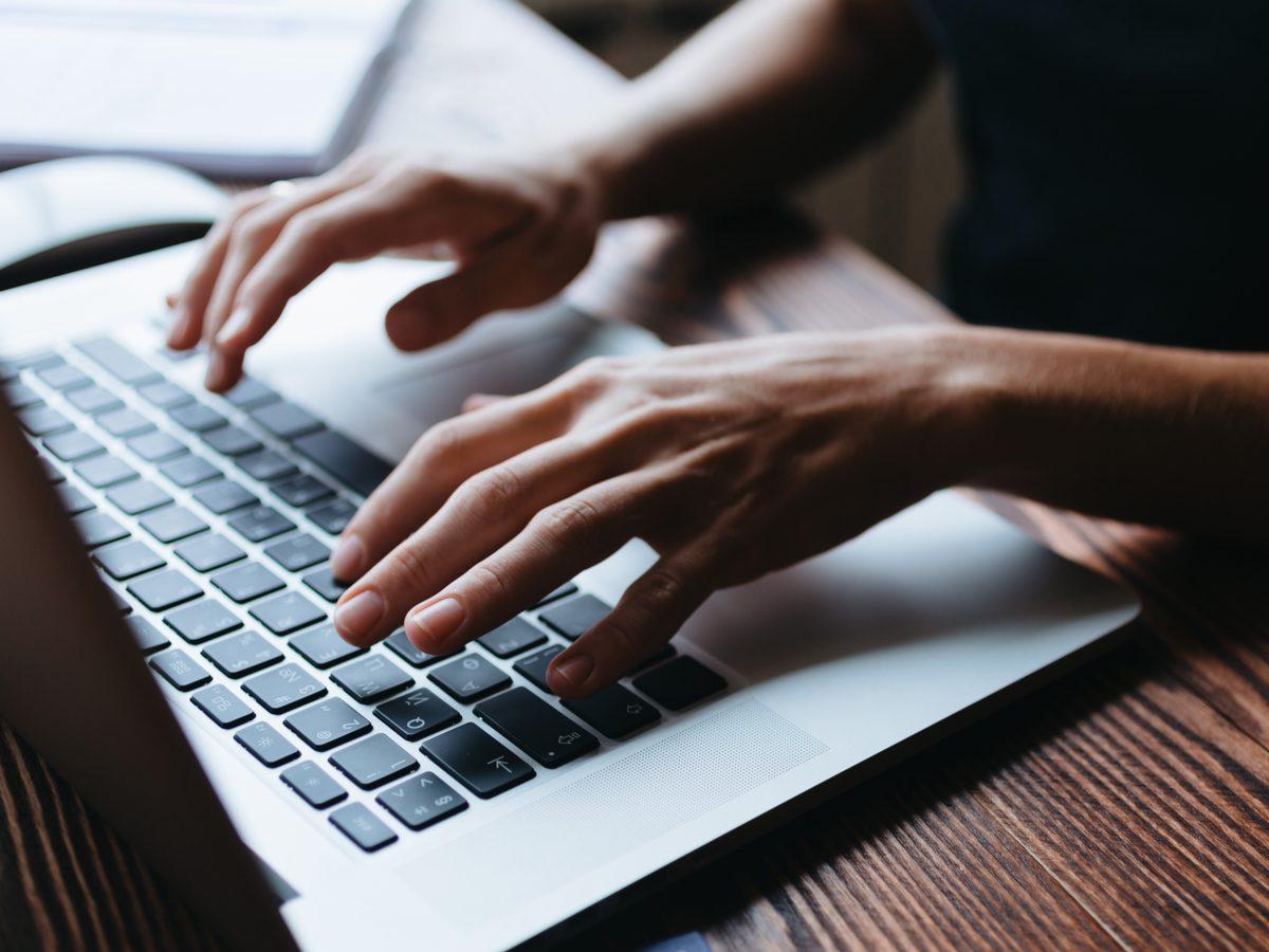 Female hand writing something on the laptop keyboard