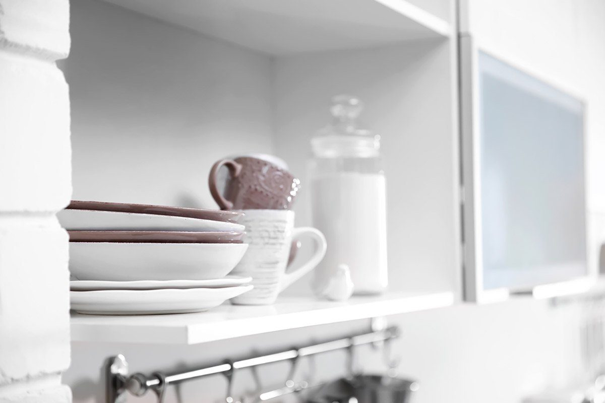 Cups and plates on a kitchen shelf.