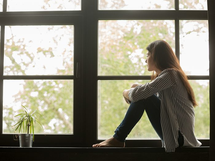 Why it's important to feel sad during COVID-19 - sad woman looking out window