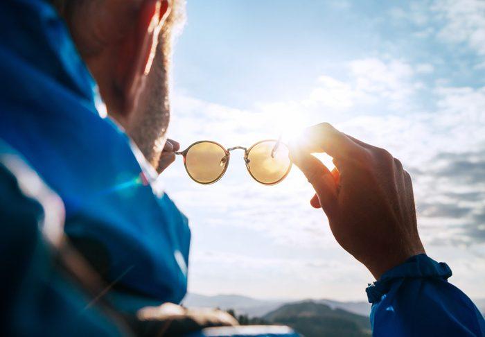Sunglasses myth - Backpacker man holding sunglasses