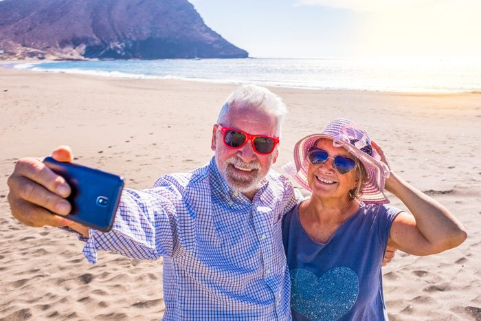 Sunglasses myths - Older couple taking selfie on beach