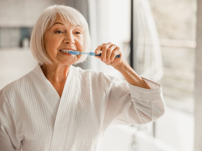 dental problems - mature woman brushing teeth