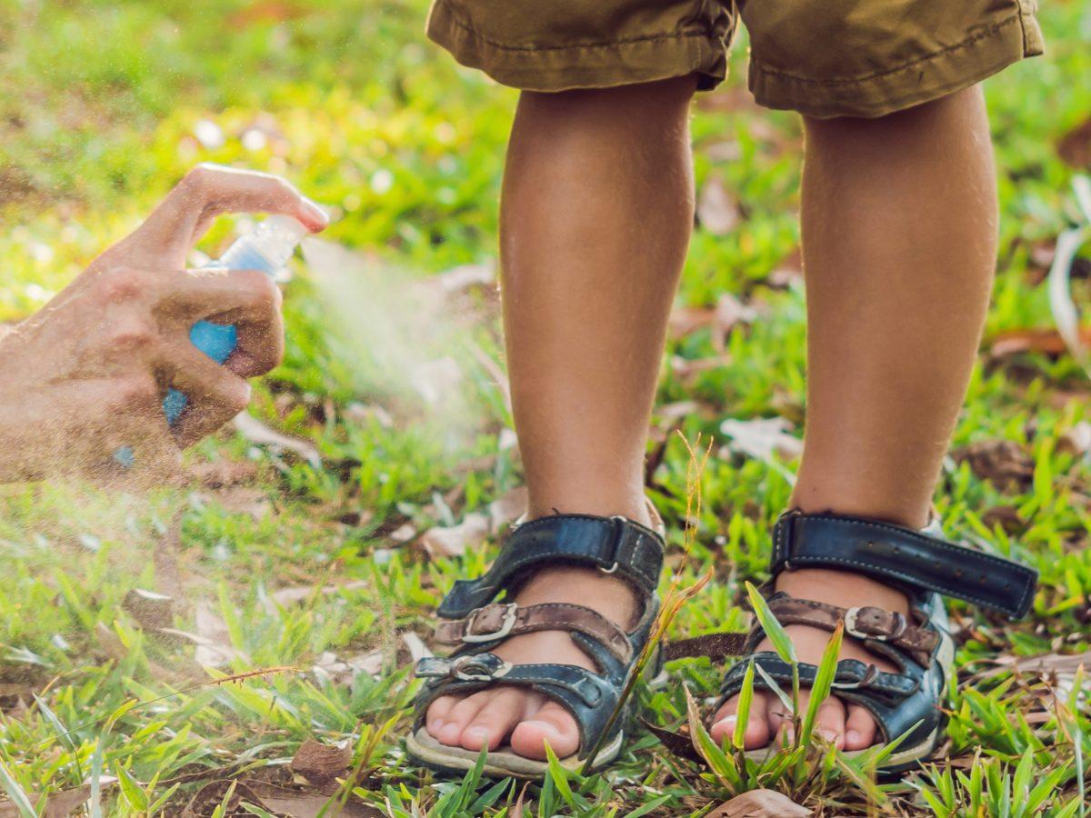 Mother applying bug spray to child's legs