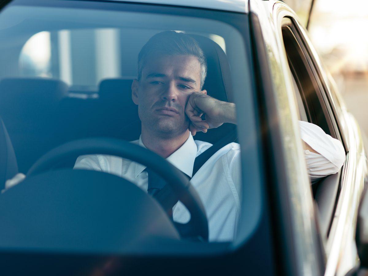 Jaded businessman looking outside of car