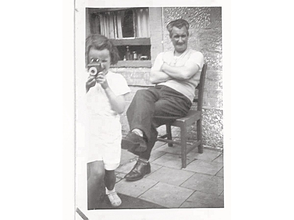 Ann as a child, camera in hand, with a smiling Papa seated behind her