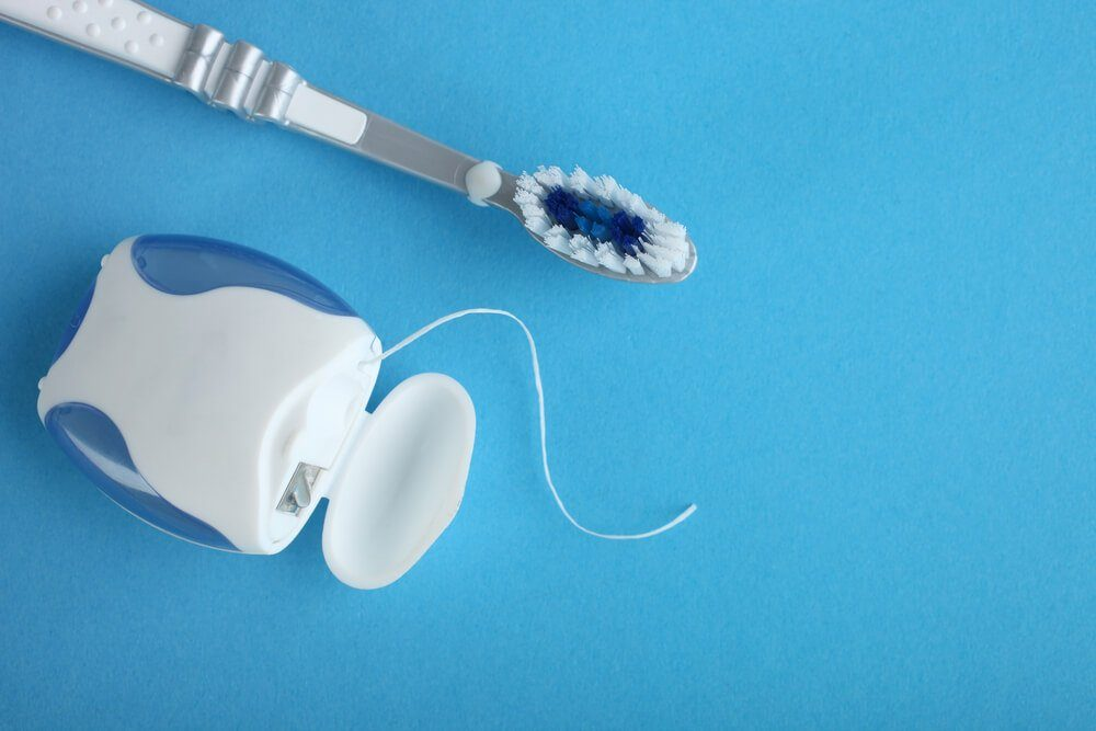 Dental floss and toothbrush on a blue background
