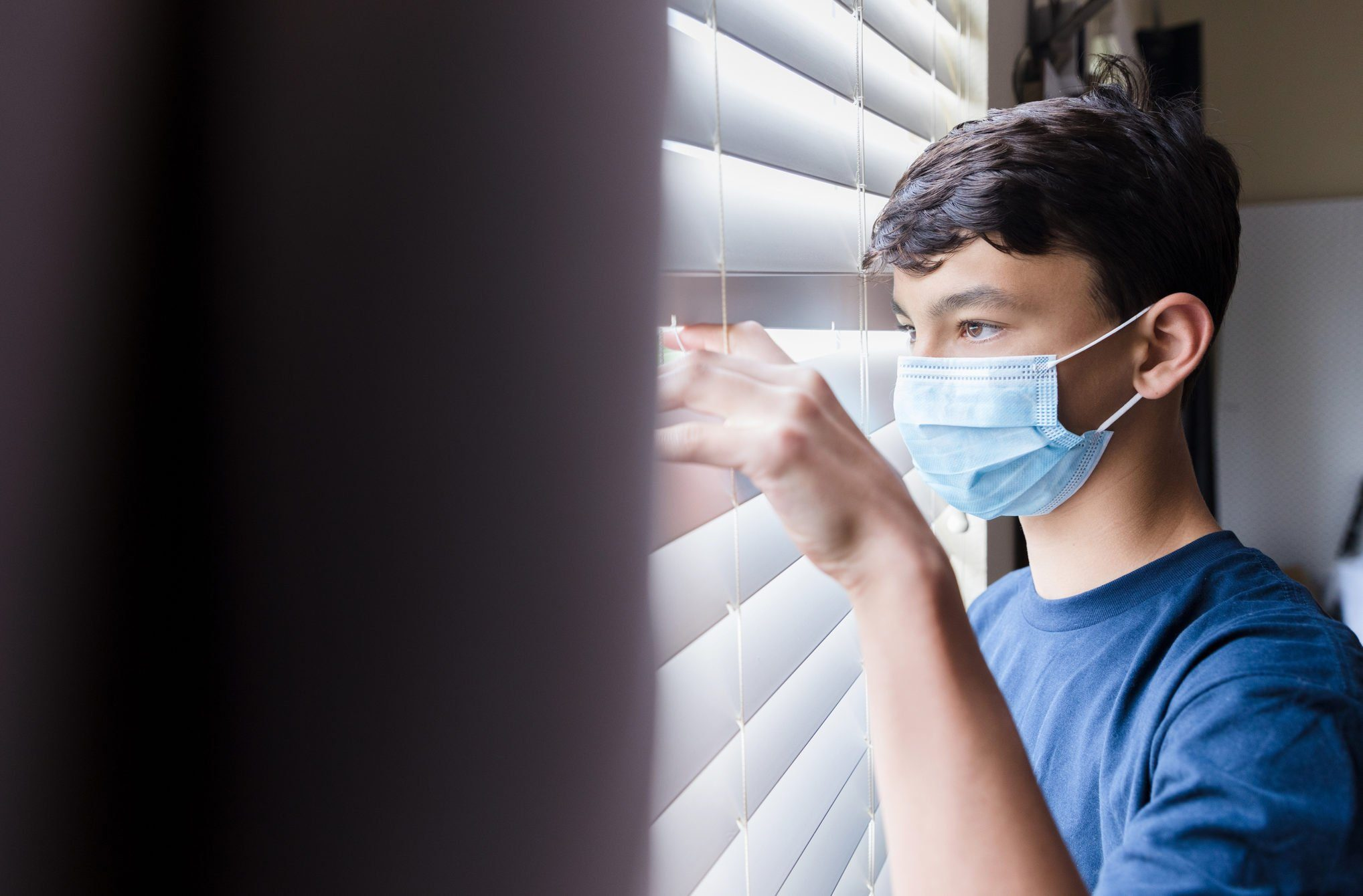 During COVID-19, quarantined boy wearing mask looks through blinds