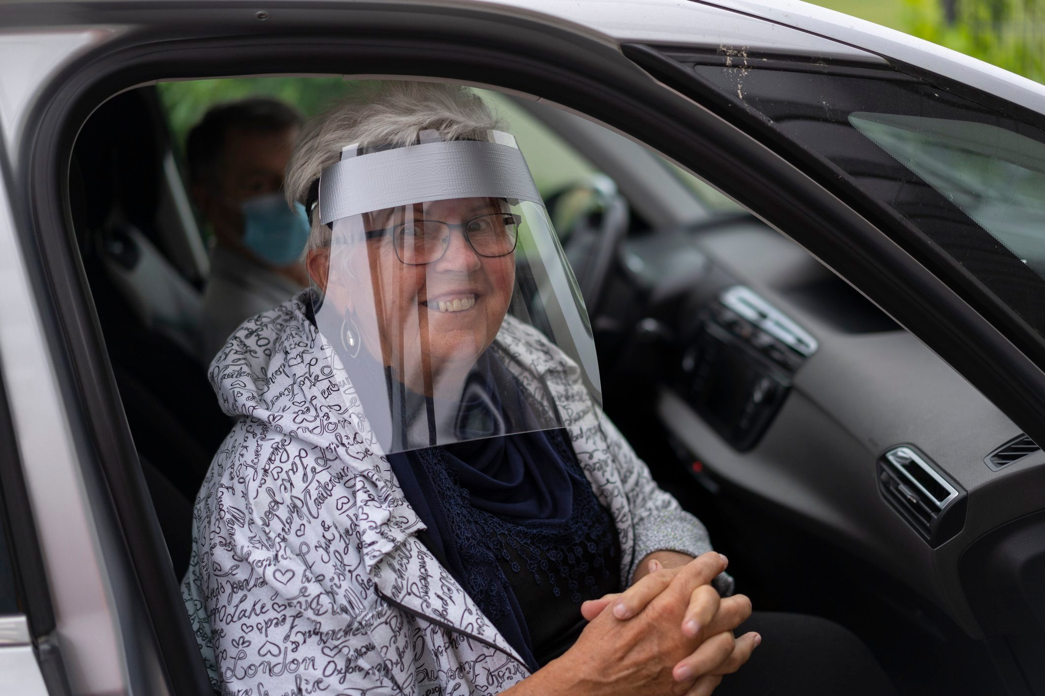 smiling elderly woman with face shield in car