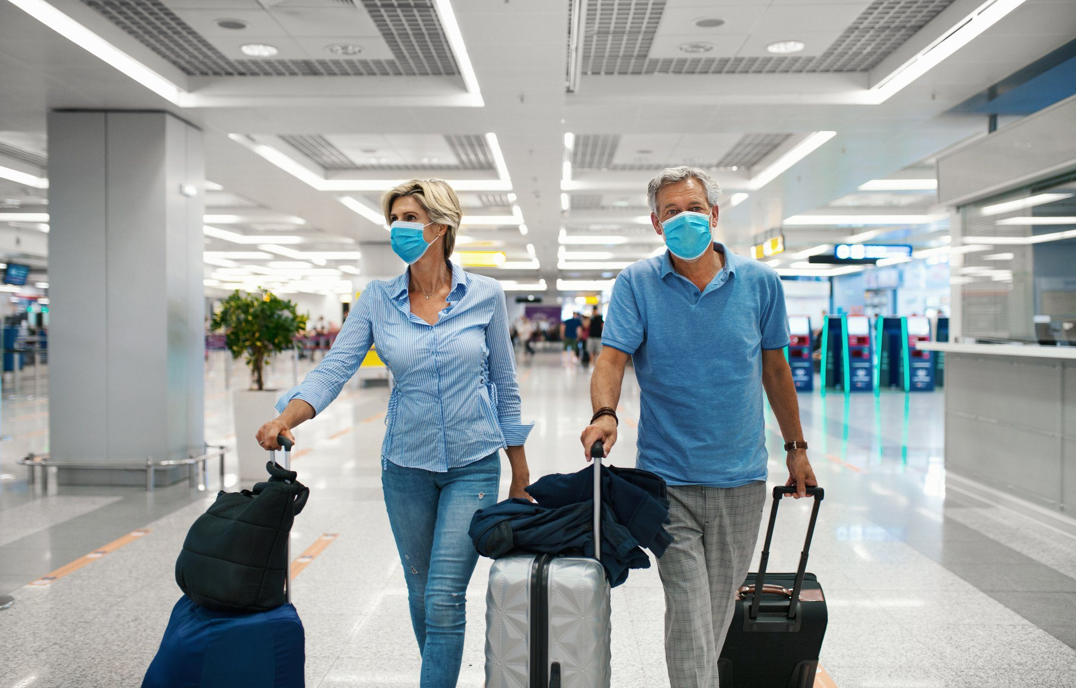 Middle aged couple at an airport during coronavirus pandemic.