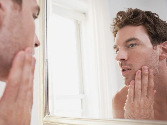 Anemia symptoms - man inspecting face in mirror