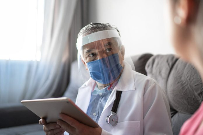 Doctor and patient on medical consultation using digital tablet at patient's house