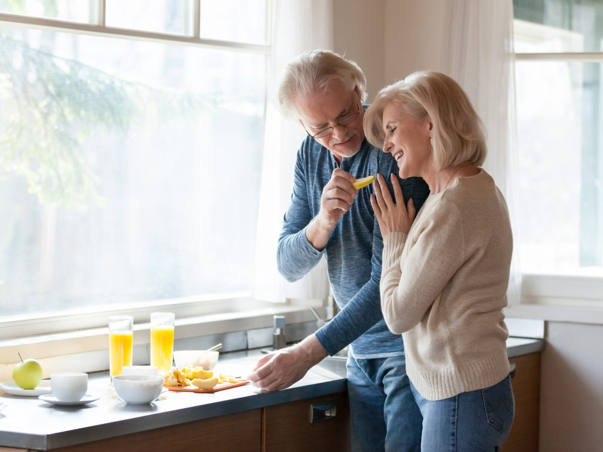 Senior couple washing up in their kitchen