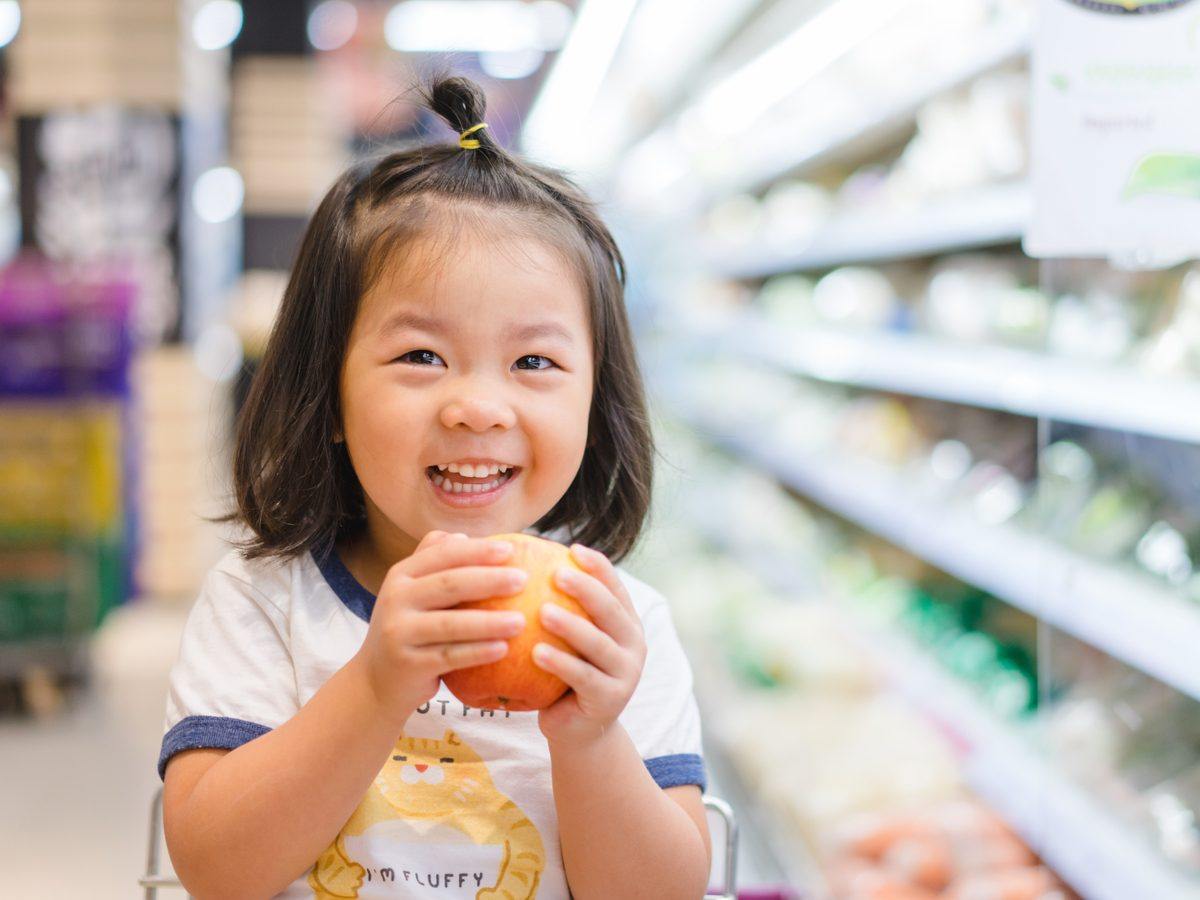 Cute little girl holding an apple in a supermarket
