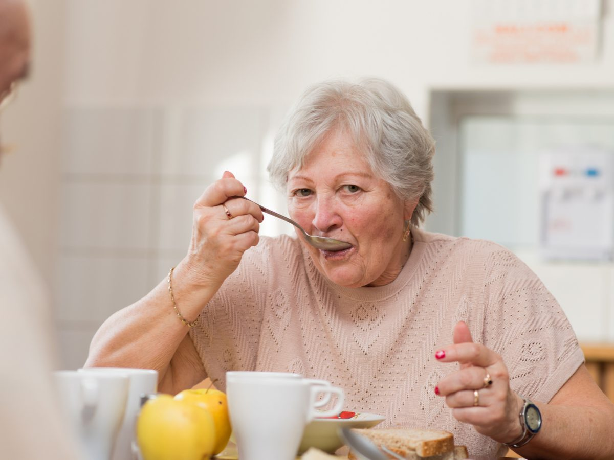 Senior woman eating breakfast at dining room table