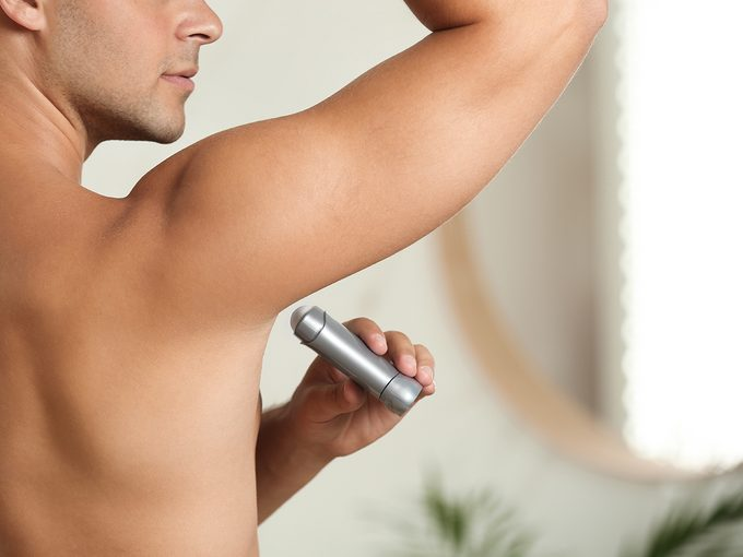 How To Sweat Less This Summer - Person applying deodorant