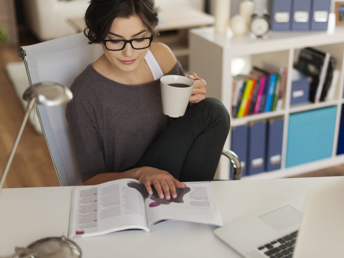 Woman drinking coffee in her home office