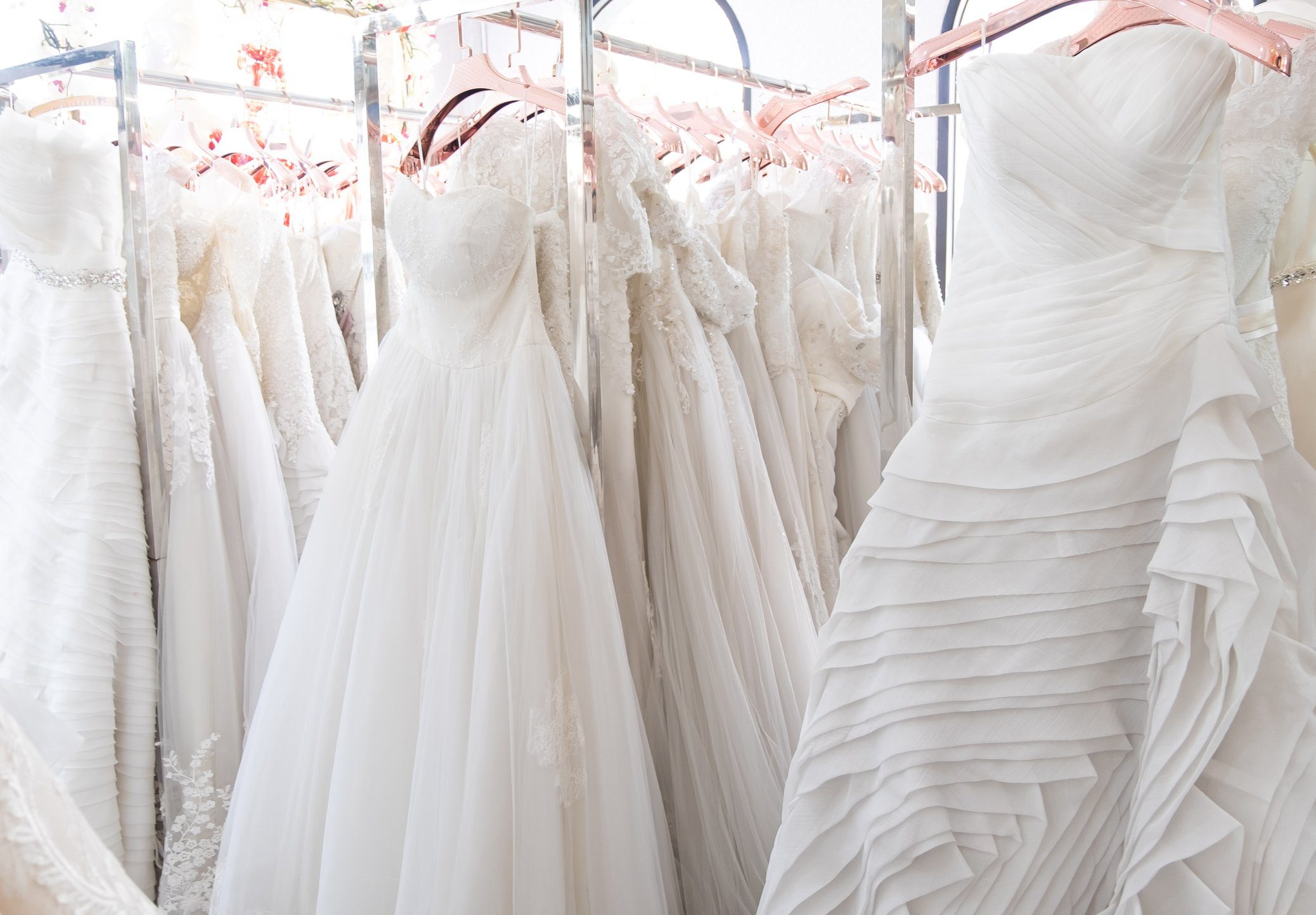 Beautiful, White bridal dress texture on background. Wedding dresses hanging on a hanger interior of bridal salon. Design, fashion modern luxury in detail.