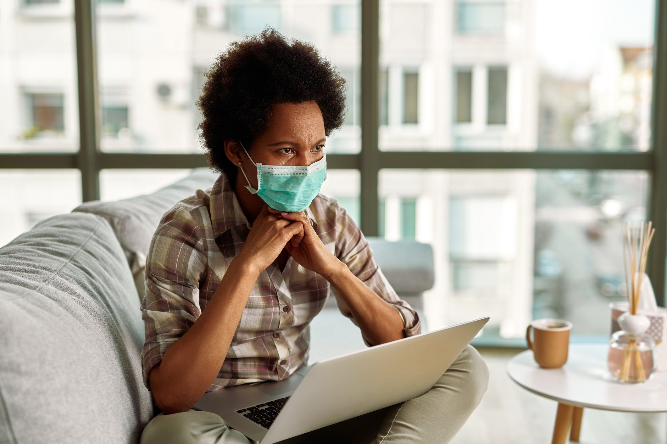 Pensive African American woman with face mask using laptop in the living room.