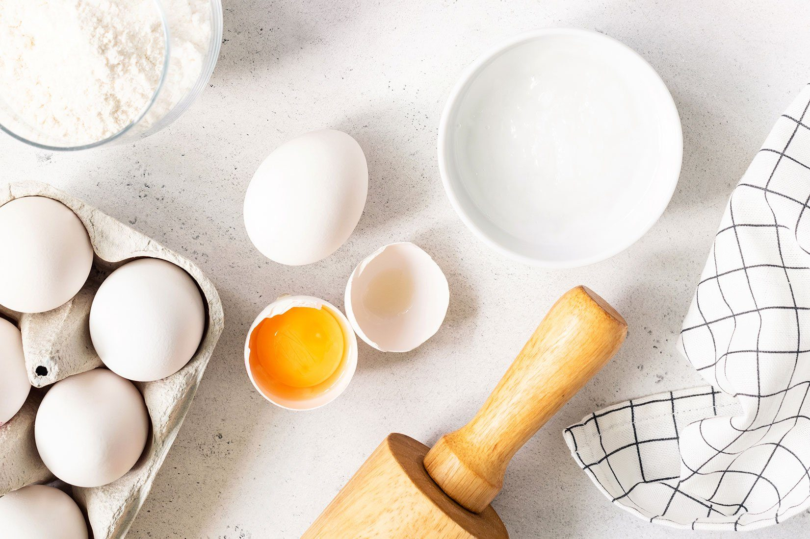 overhead view of eggs, rolling pin, baking soda, bowl on a white counter top