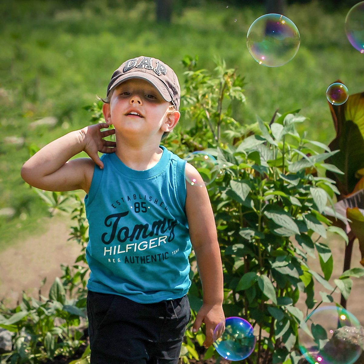 In the backyard photography - boy chasing bubbles