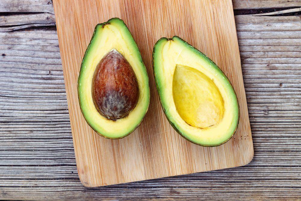 ripe avocado sliced in half on a cutting board