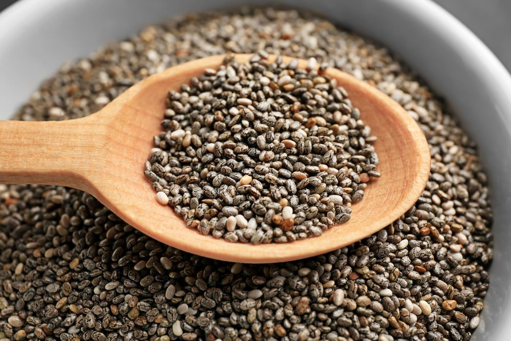 Chia seeds in wooden spoon over bowl
