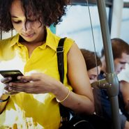 Text slang - Young woman using a smartphone in a subway